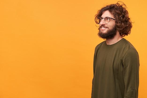 Крупным планом вдохновленный рад красивый бородатый парень в очках, стоя боком