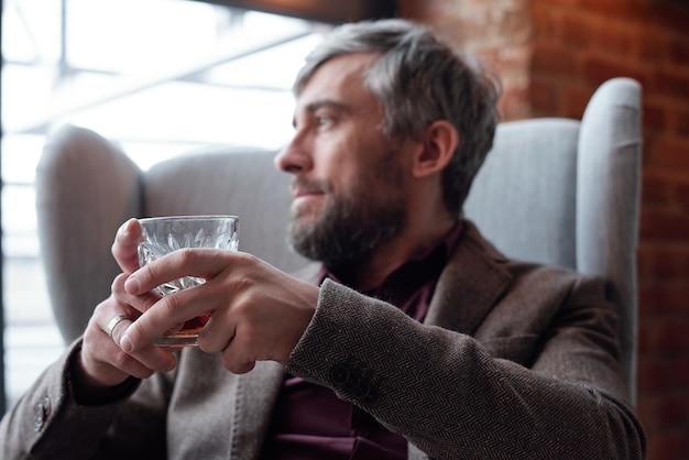 リビングルームの肘掛け椅子に座ってハードリキュールを楽しんでいるジャケットを着た内省的な中年男性のクローズアップ