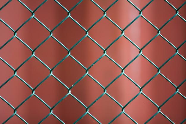 격리 된 페인트 간단한 기하학적 검은 철 금속 와이어 체인 링크 울타리 이온 어두운 빨간색 배경의 근접. 울타리, 보호 및 인클로저 개념.