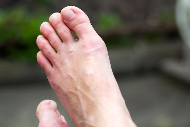 ぼやけた灰緑色のシーンで休んでいるつや出しされていない爪を持つ女性のきれいな白い乾燥した足の孤立したペアのクローズアップ。ヘルスケア、化粧品、衛生の概念。