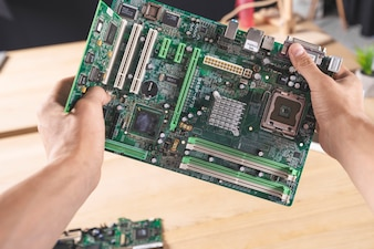 Close-up of IT male technician holding computer mainboard
