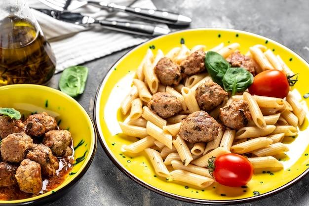 黄色いプレートと灰色の表面にトマトソースとミートボールを添えたイタリアンパスタのクローズアップ。食品レシピ面