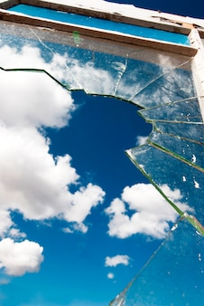 Close up of jagged broken window with blue sky in background