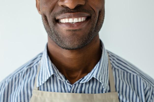 Крупным планом радостный афро-американский мужчина, выражающий радость у белой стены