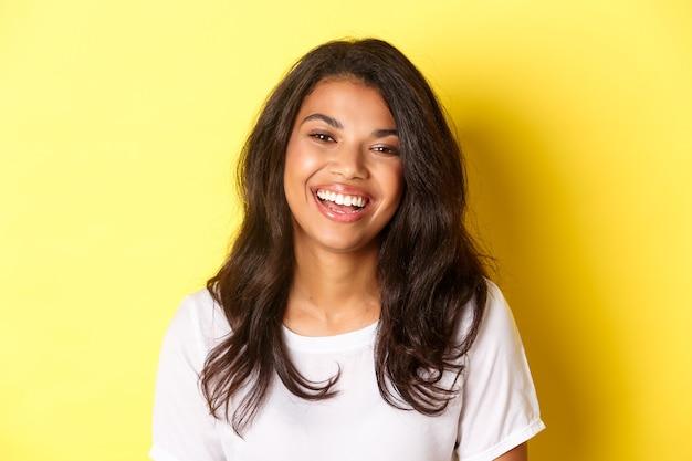 Крупный план радостной и красивой афро-американской женщины, смеющейся и выглядящей счастливой, стоя на желтом фоне.
