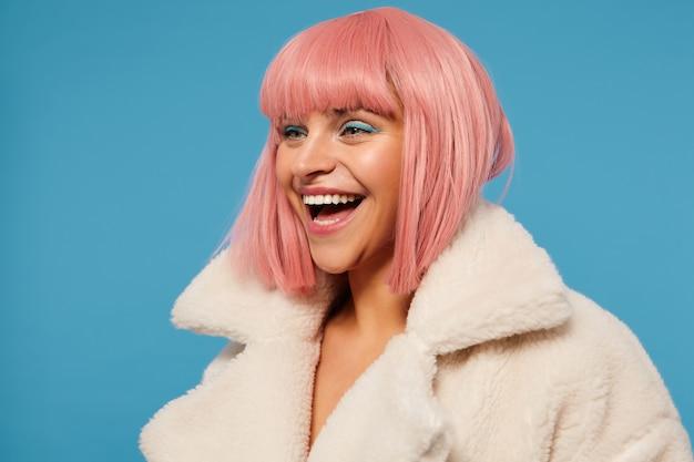 짧은 분홍색 밥 머리가 유쾌하게 옆으로보고 행복하게 웃고 멋진 옷을 입고 파란색 배경에 서있는 즐거운 아름다운 젊은 여성의 근접