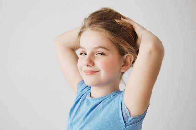 찾고, 밝게 웃 고 손으로 금발의 긴 머리를 잡고 파란색 티셔츠에 즐거운 어린 소녀 닫습니다. 공간을 복사하십시오.