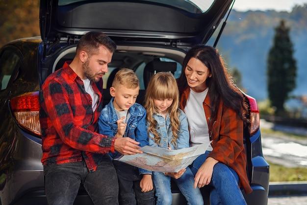 十代の子供たちと休暇を取り、車で正しい道を選択するためにロードマップを使用している楽しい楽しい家族のクローズアップ