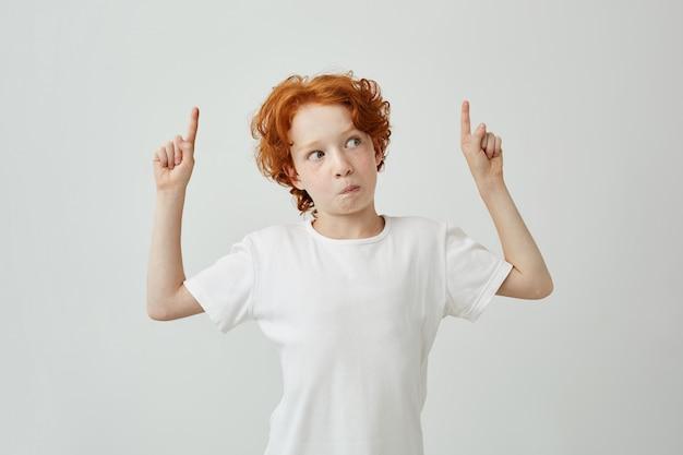 驚きと好奇心が強い表情で逆さまに指している白いtシャツでうれしそうな赤い髪の少年のクローズアップ