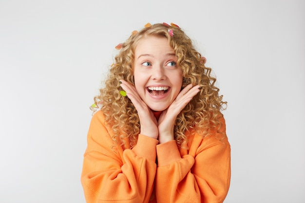 Крупным планом радостная улыбающаяся милая нежная милая блондинка смотрит на правую сторону, чувствует себя взволнованной, удивленной, держит ладони возле лица, одетая в огромный оранжевый свитер, изолированную на белой стене