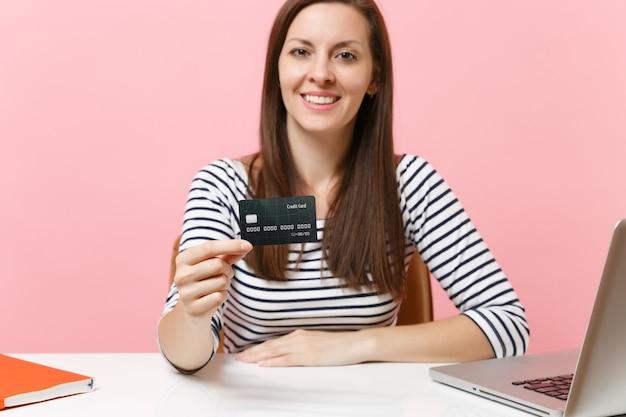 신용 카드 작업을 들고 캐주얼 옷을 입은 즐거운 여성이 현대적인 pc 노트북이 있는 흰색 책상에 앉아 있습니다.