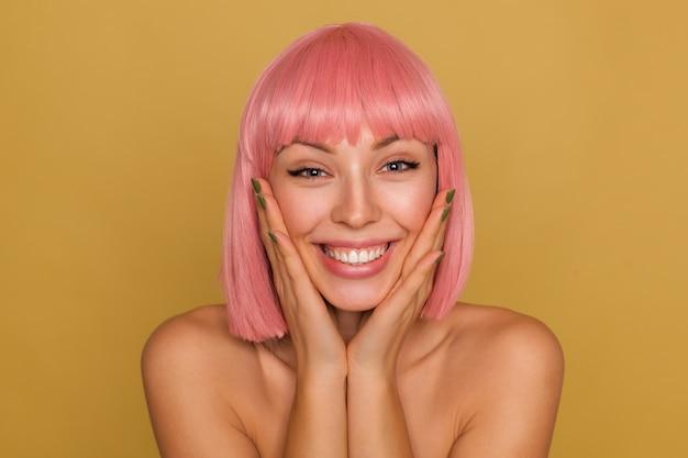 겨자 벽 위에 절연 넓은 미소로 행복하게 보면서 짧은 유행 머리가 그녀의 뺨에 손바닥을 유지하는 즐거운 젊은 파란 눈 분홍색 머리 여성의 근접