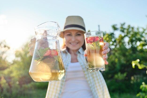 Крупный план кувшина и стакана с натуральным травяным мятным клубничным напитком в руках женщины
