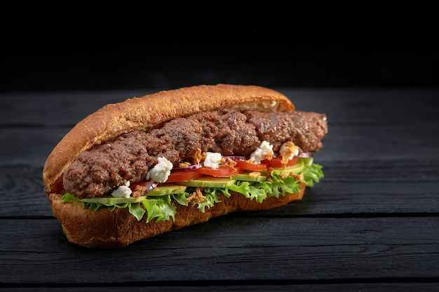 Закройте бутерброд кебаба на черной деревянной предпосылке. концепция быстрого питания