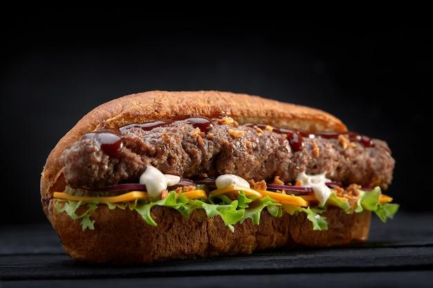 Закройте сэндвич с шашлыком на черном деревянном пространстве