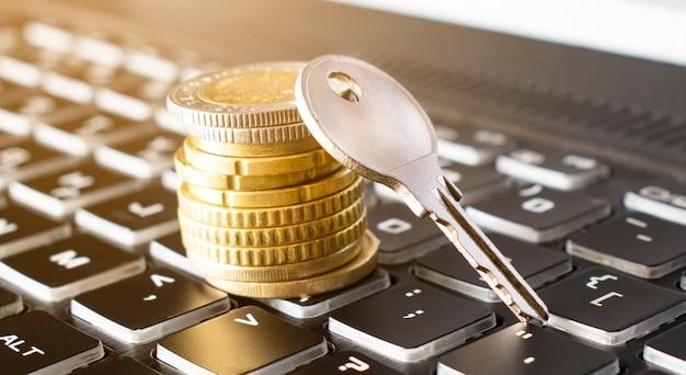 키의 근접 및 블랙 키보드에 동전의 스택. 보험 개념