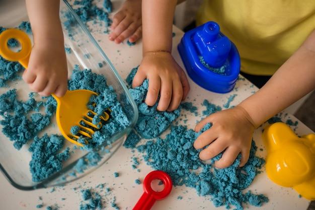 Конец-вверх кинетического песка и набора ящика с песком. руки ребенка играют с песком.