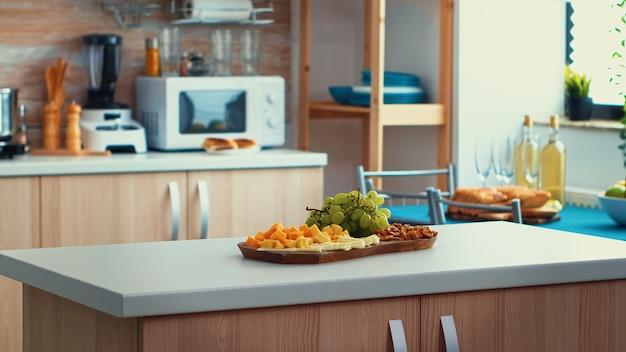 Закройте кухонный стол с сыром и виноградом на нем. открытый интерьер комнаты с дневным освещением, дизайнерская роскошная архитектура жилого убранства с обеденным столом в центре комнаты.