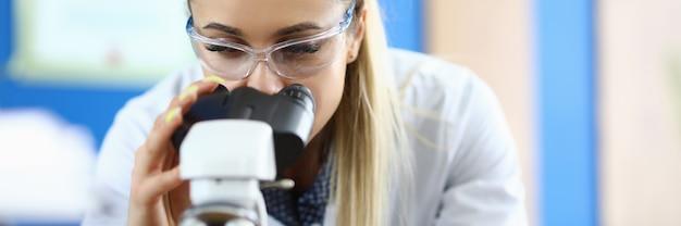 サンプルの分析を行っている実験助手のクローズアップ。顕微鏡でdnaコンポーネントを検査する作業員。スタンドの試験管。分析と化学の概念