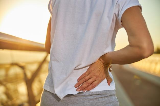Крупным планом дамы в белой рубашке с болью в спине, стоя на улице