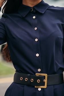 屋外に立っている間スタイリッシュな革のストラップで黒のドレスを着ている女性のクローズアップ。女性のファッション
