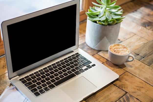 カフェテリアのテーブルの上のコーヒーカップによるラップトップのクローズアップ