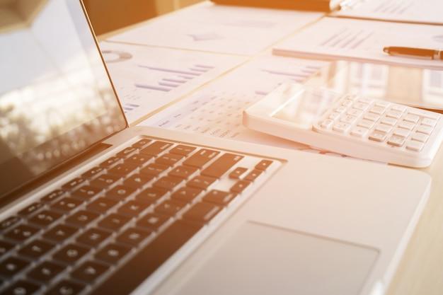 사무실 바탕 화면에 노트북, 금융 문서 및 계산기의 근접