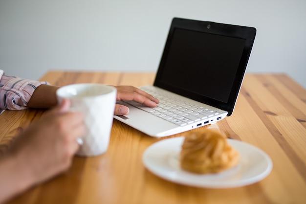 空白の画面とコーヒーやお茶のカップと女性の手でラップトップのクローズアップ
