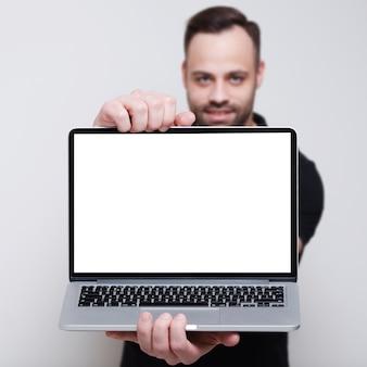 웃는 남자의 손에 빈 화면이 노트북의 클로즈업