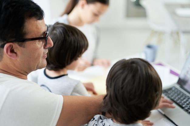 집에서 일하고 아이들을 보면서 노트북을 사용하는 라틴계 아버지의 클로즈업. 프리랜서, 잠금, 가족 개념