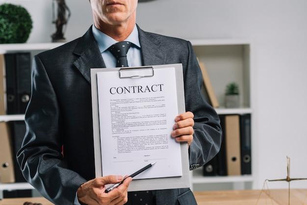 Крупный план адвоката, который показывает юридическое соглашение с ручкой
