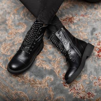 Крупный план кожаных модных осенних черных сапог со шнуровкой на женских ножках