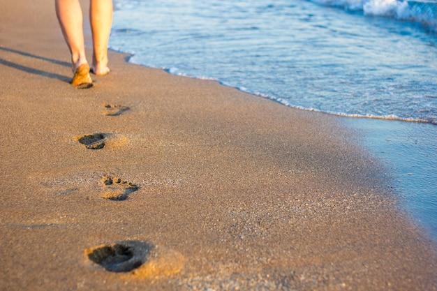 足のクローズアップ、砂と海の波の足跡