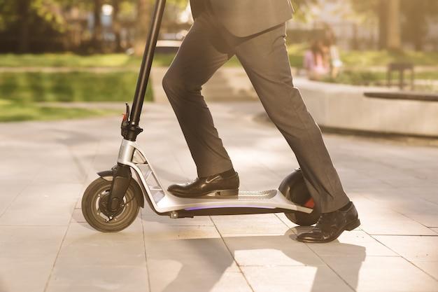 Крупным планом ноги человека в костюме, езда на электросамокате в городе, неизвестный бизнесмен в классическом костюме
