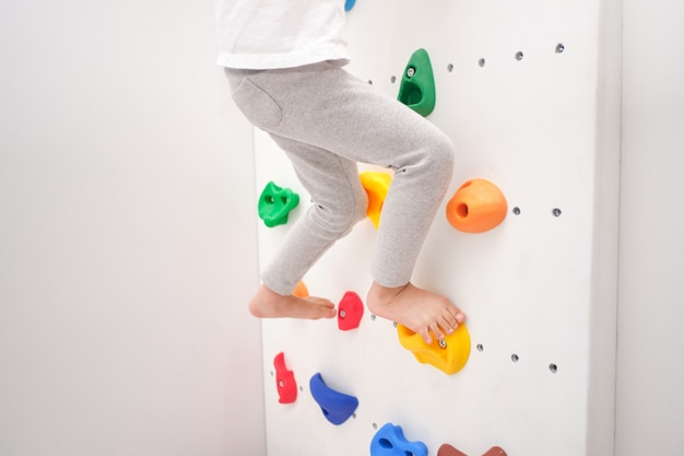 自宅の屋内の小さな岩壁に登ろうとして楽しんでいる小さな幼稚園の男の子の足のクローズアップ