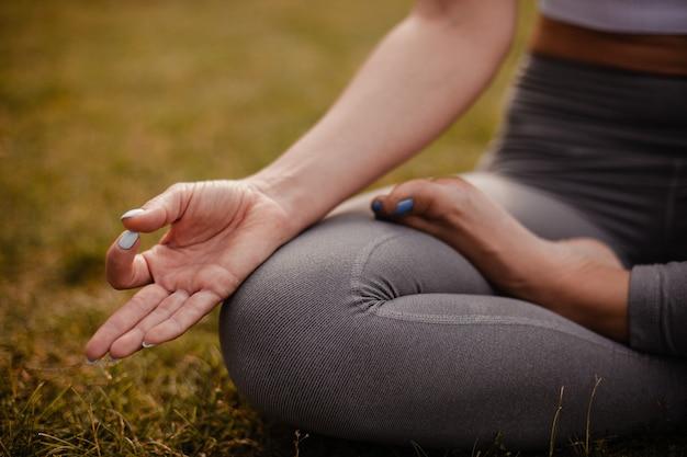 클로즈업 - 연꽃 위치에 앉아 명상을 하고 숲속의 여름 일몰에 지안 무드라에 손가락을 대고 있는 여성의 다리 클로즈업.