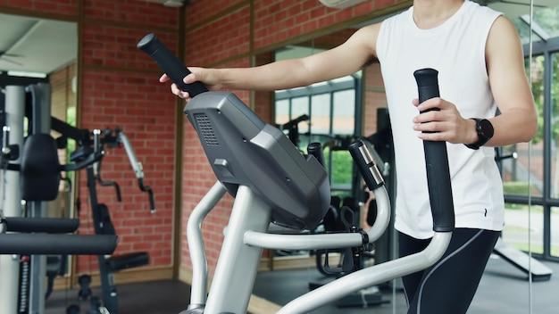 フィットネスセンターで楕円形のトレーナーを使用して若いスポーツ男性の足のクローズアップ
