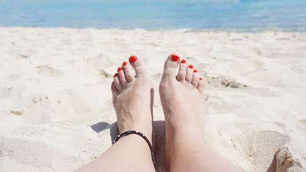 足のクローズアップ。ビーチで夏の日を過ごしながら海でリラックスする女性。