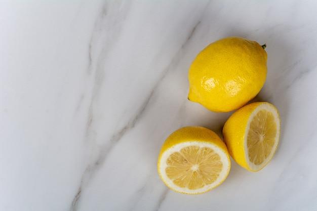 레몬과 레몬 조각 대리석 테이블에 클로즈업. 요리와 음식 개념.