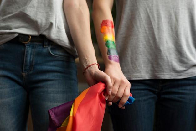 手でlbgtフラグを保持しているレズビアンのカップルのクローズアップ