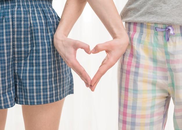 自分の手で白い背景で隔離の心を作るレズビアンの若いカップルのクローズアップ