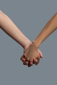 Крупный план светлокожих и темнокожих людей, держащихся за руки