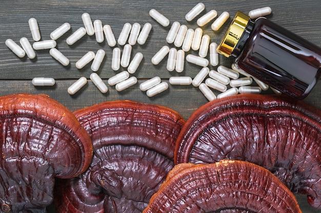 霊芝キノコ、霊芝キノコ、木製テーブルのボトルモックアップとカプセルのクローズアップ