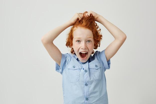 悲鳴を上げる手で髪を保持しているそばかすのある美しい生姜少年のクローズアップ