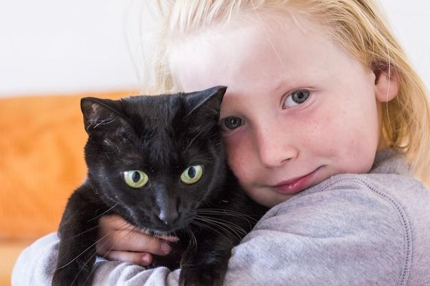 自宅のリビングルームで子猫と遊んでいる小さな男の子のクローズアップ。若い猫と少年の肖像画。家を見つめているペットの猫とかわいい男の子。愛情と思いやりのあるペットの動物