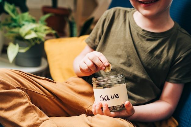 小さな子供の子供の男の子の手をつかんで、保存してガラスの瓶にスタックコインを入れてクローズアップ