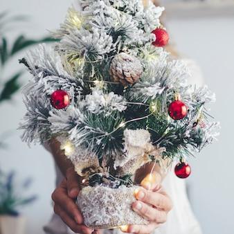 後ろに隠された女性の手から示された小さなクリスマスツリーのクローズアップ。休日12月のお祝いシーズンライフコンセプト。白色の背景