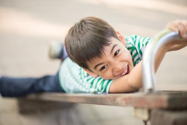 遊び場でスライダーを再生するかわいい少年のクローズアップ