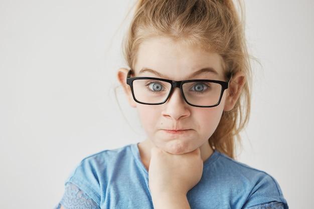 Крупным планом маленькая милая девушка с большими голубыми глазами и светлыми волосами, глядя с выражением сердитое лицо и поднятые брови в очках.