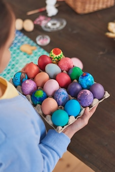 휴일을 위해 칠해진 부활절 달걀이 있는 쟁반을 들고 있는 어린 소녀의 클로즈업